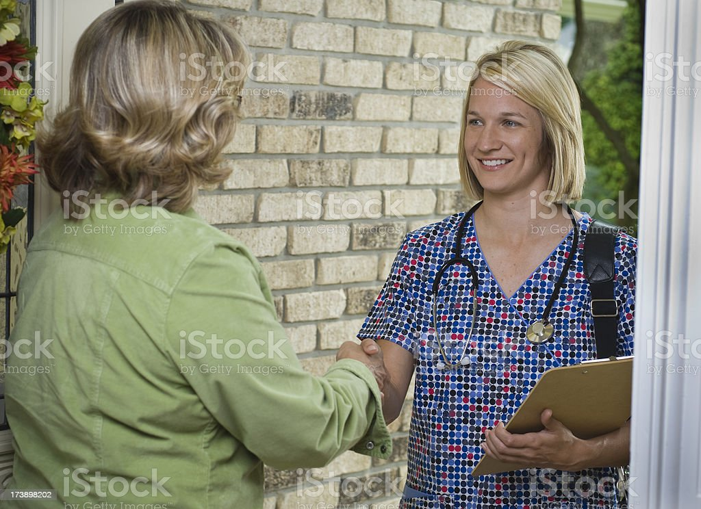 Nurse at front door of residence stock photo