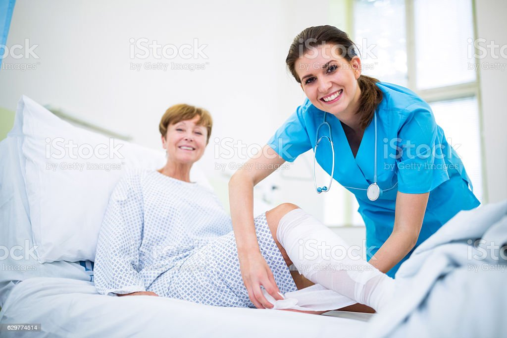 Nurse bandaging leg of patient stock photo