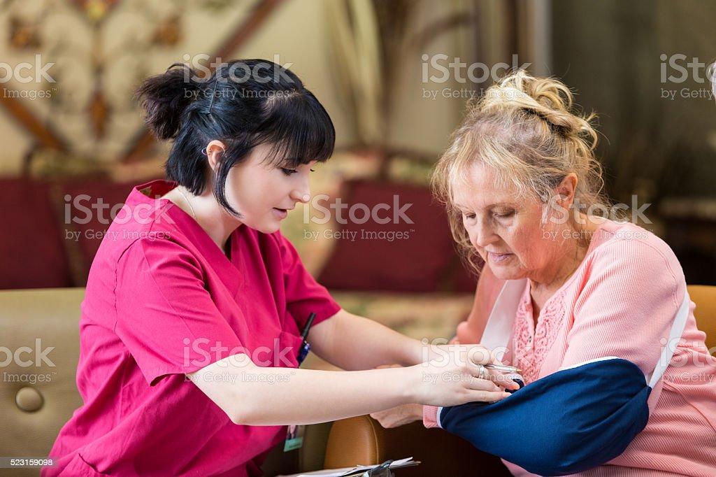 Nurse carefully examines senior woman's injured arm stock photo