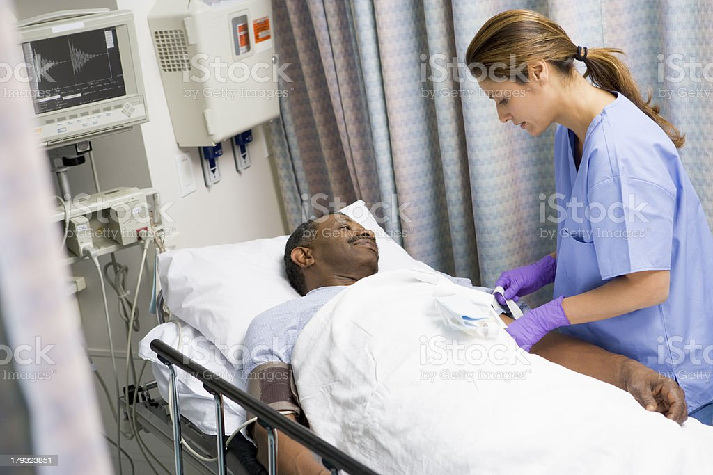 Nurse caring for a patient in a hospital bed stock photo