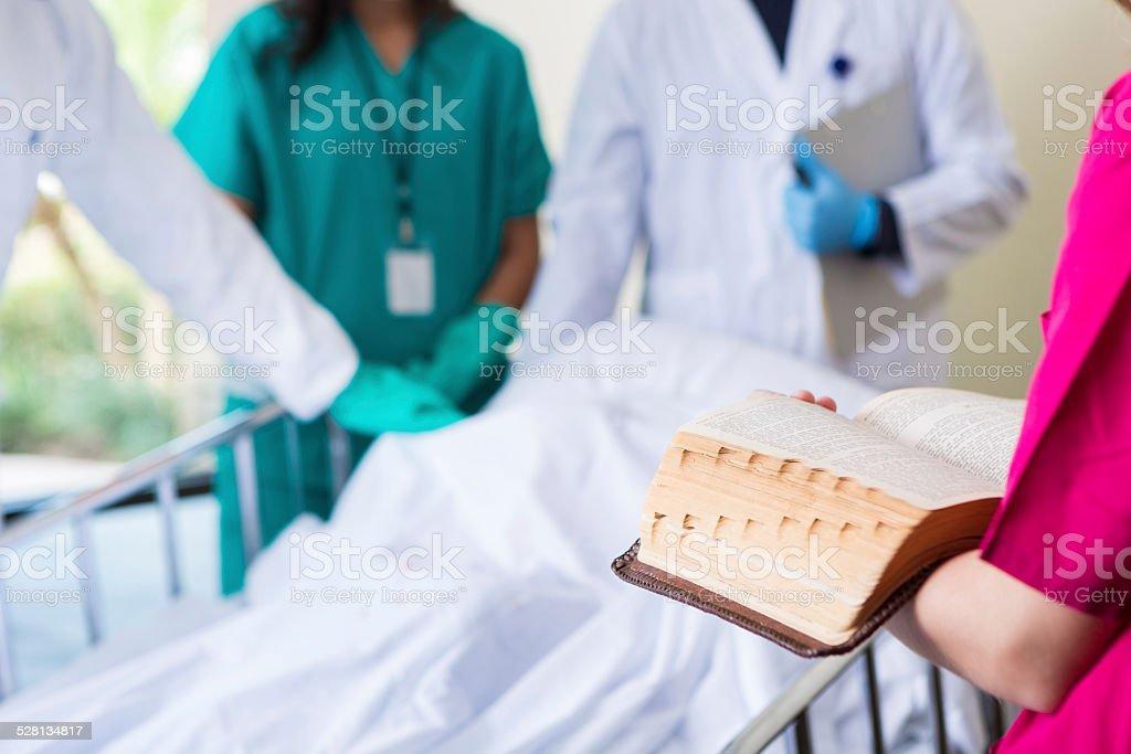 Nurse chaplain reading Bible in hospital room of deceased patient stock photo