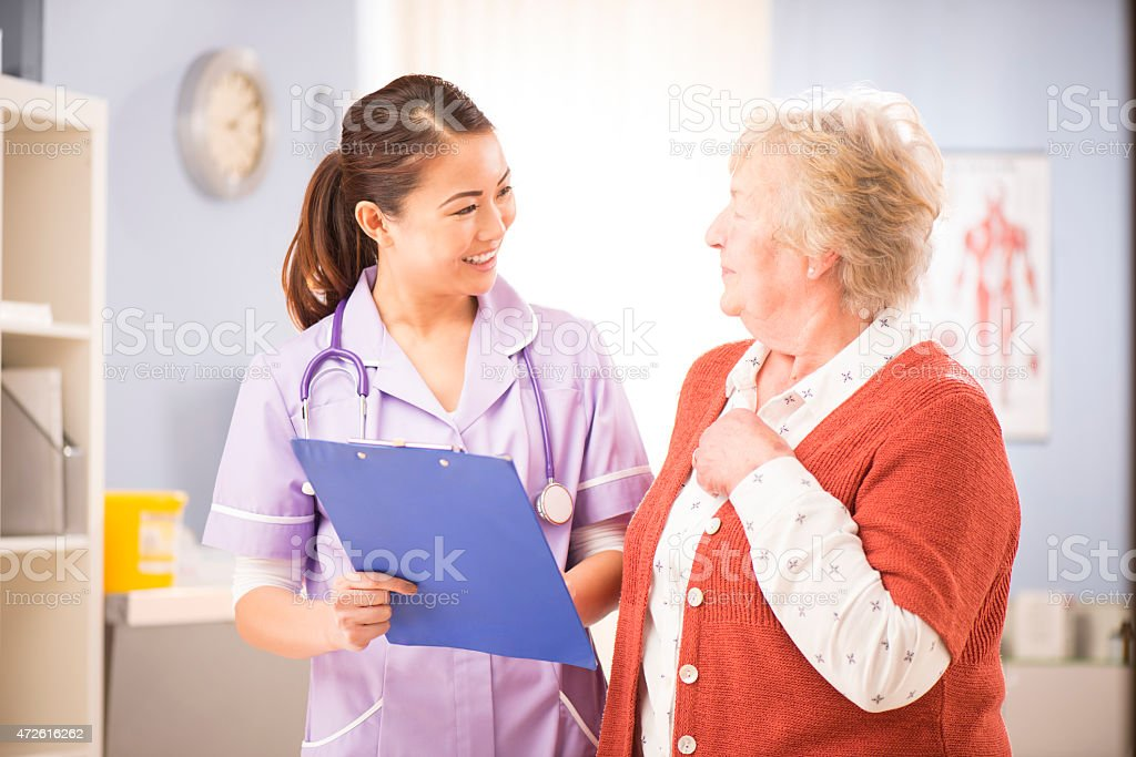 nurse chats to senior patient stock photo