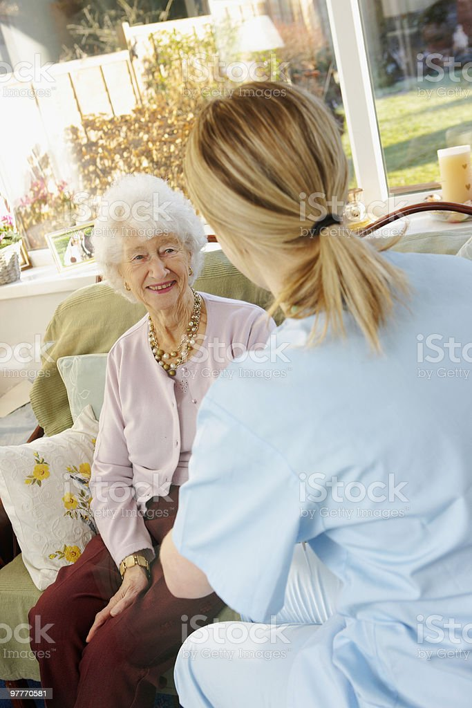 Nurse chatting to old lady in a care home royalty-free stock photo