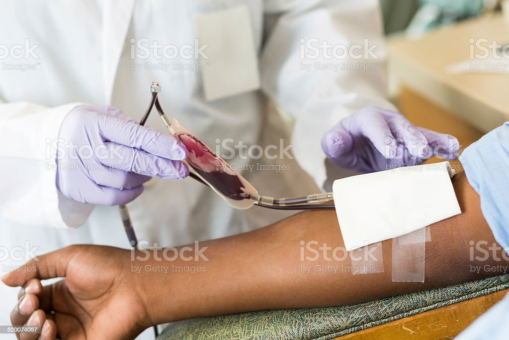 Nurse checking bag of blood while patient gives donation stock photo