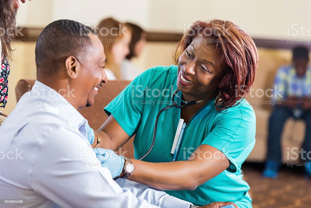 Nurse checking blood pressure for mature African American man stock photo
