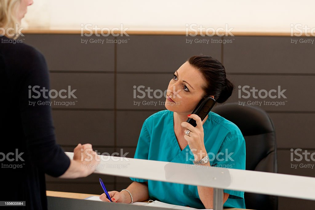 nurse checking in female patient at the reception stock photo