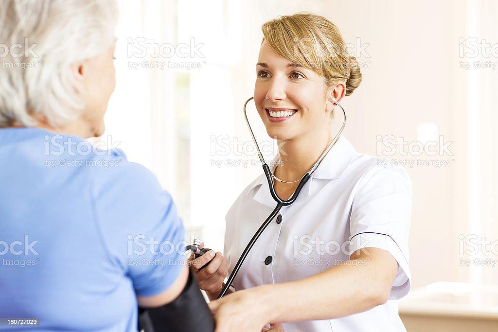 Nurse Checking Senior Female Patient's Blood Pressure. royalty-free stock photo