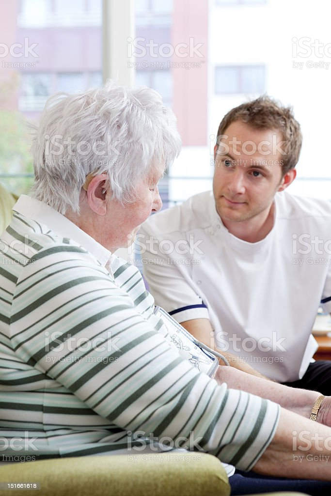 Nurse checking senior ladys blood pressure royalty-free stock photo