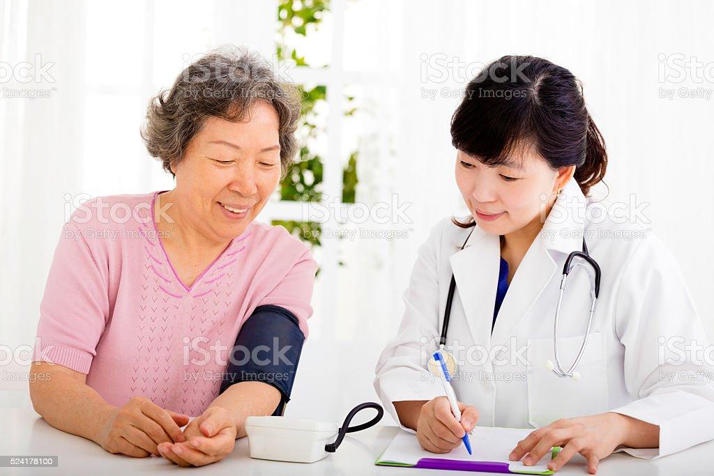 nurse checking senior woman blood pressure stock photo