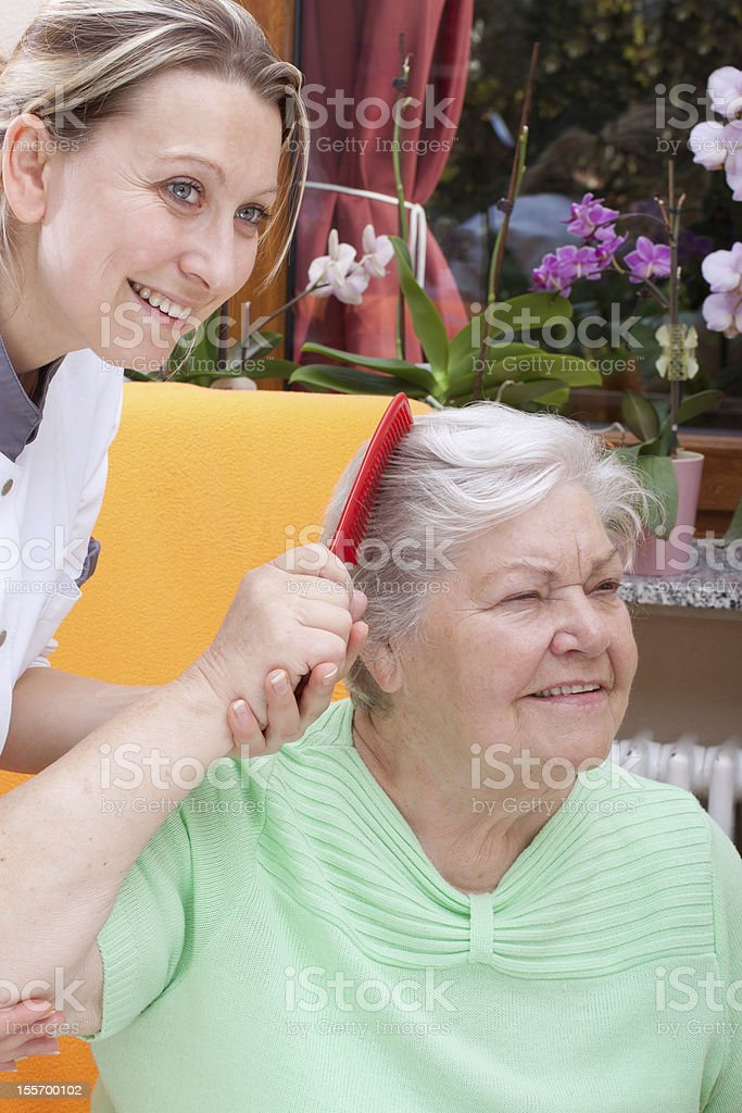 Nurse combs the hair of a senior royalty-free stock photo