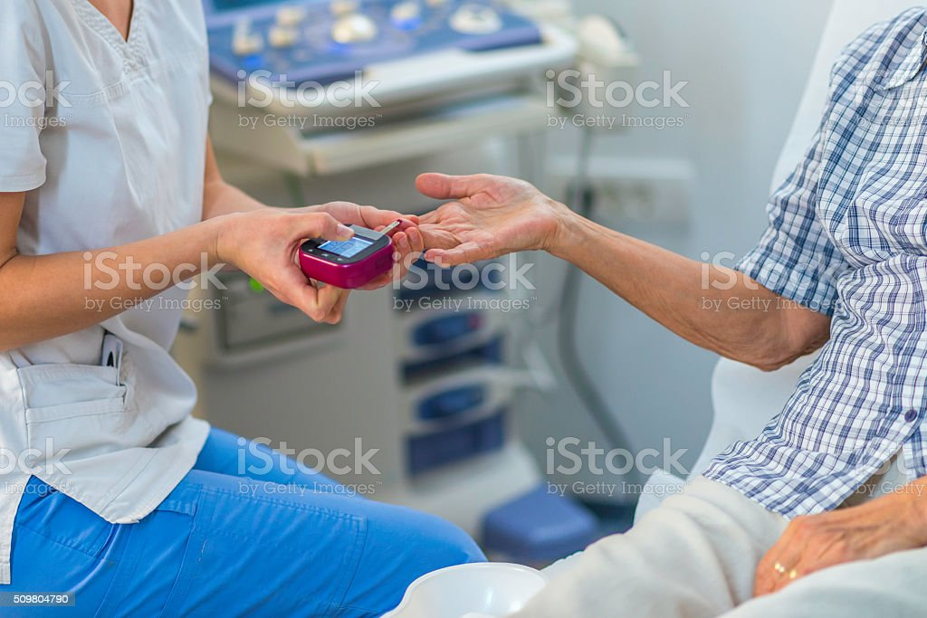 Nurse conducting a blood sugar test on an older woman stock photo