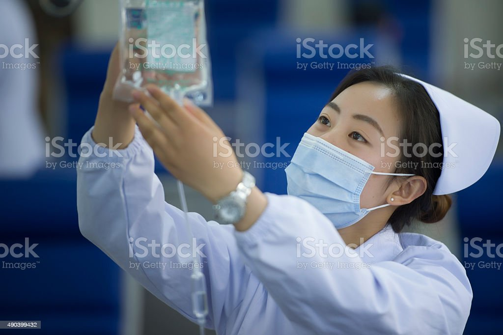 Nurse connecting an intravenous drip in hospital room stock photo