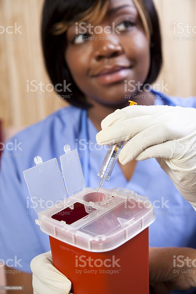 Nurse demonstrating proper disposal of medications. Sharps container. Needle. stock photo