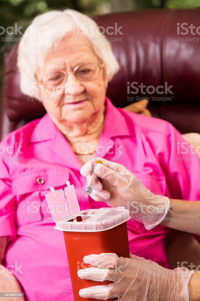Nurse demonstrating proper disposal of medications, syringes. stock photo