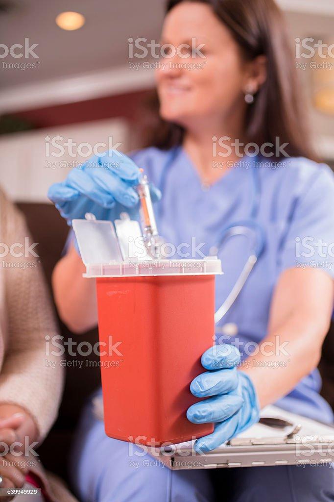 Nurse demonstrating proper disposal of syringes. stock photo
