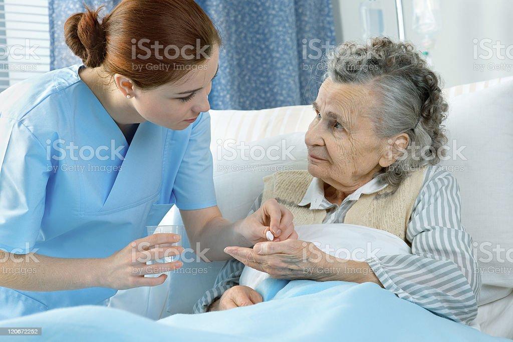 Nurse dispensing medication to elderly woman in bed royalty-free stock photo