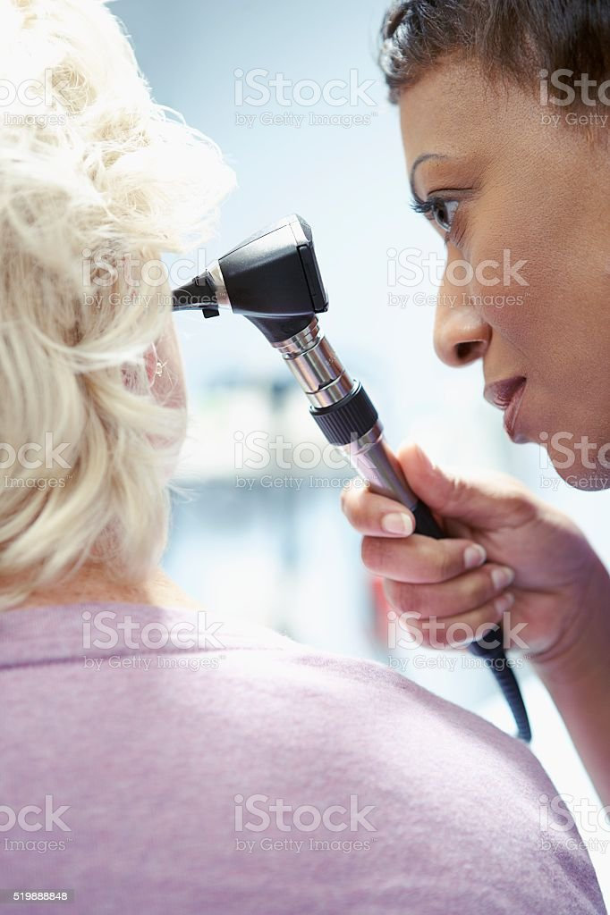 Nurse examining a patient's ear stock photo