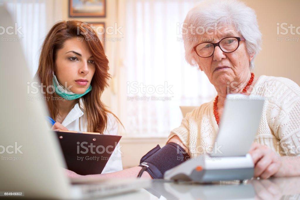 Nurse examining blood pressure for senior patient. Home care concept. stock photo
