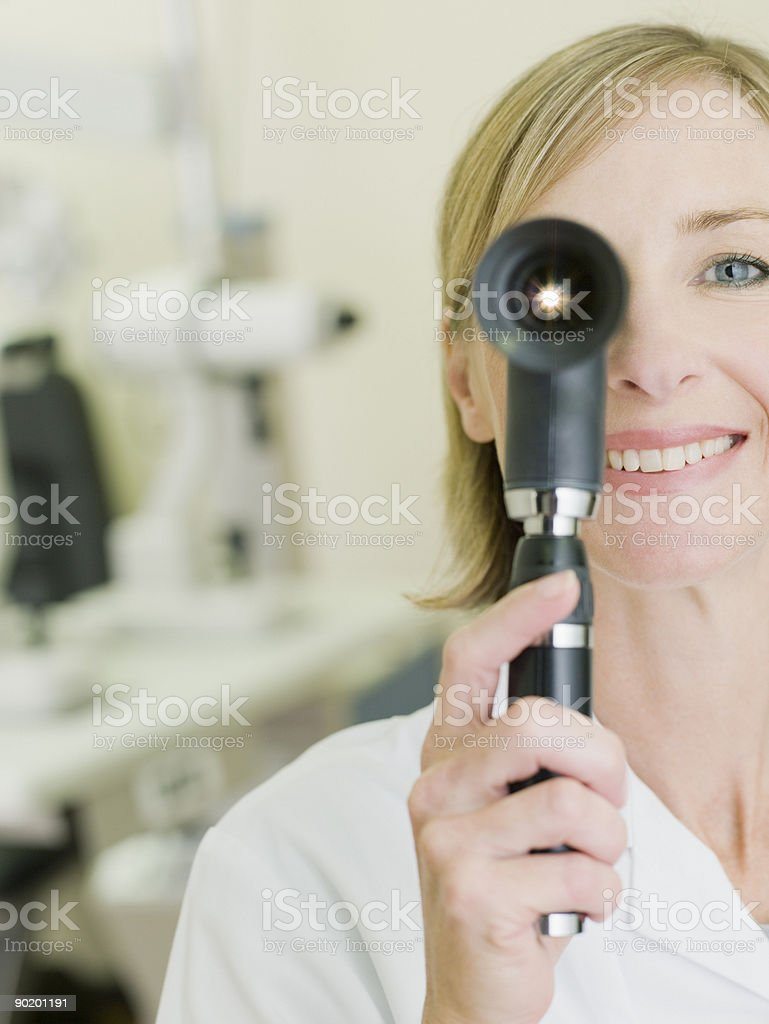 Nurse examining patient with opthalmoscope stock photo
