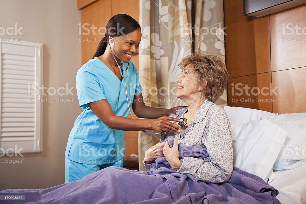 Nurse examining senior woman in hospital room stock photo