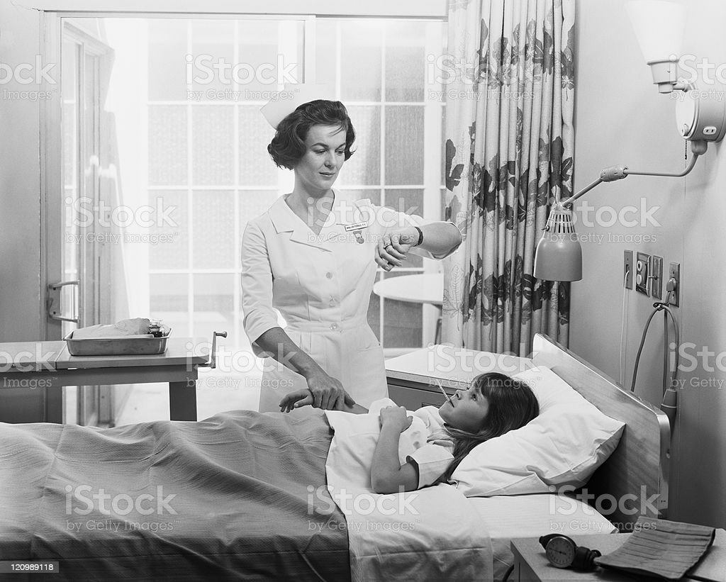 Nurse examining temperature and taking pulse of girl stock photo