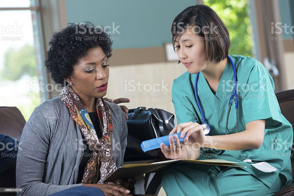 Nurse explaining medicine schedule to patient stock photo