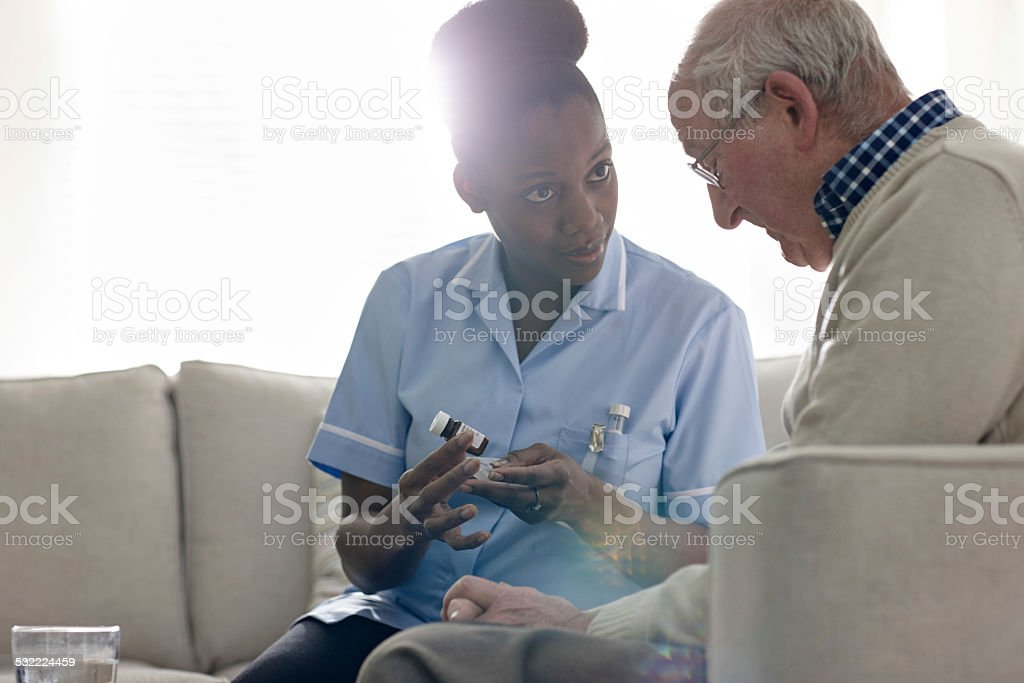 Young female nurse explaining the medication to senior man in care...