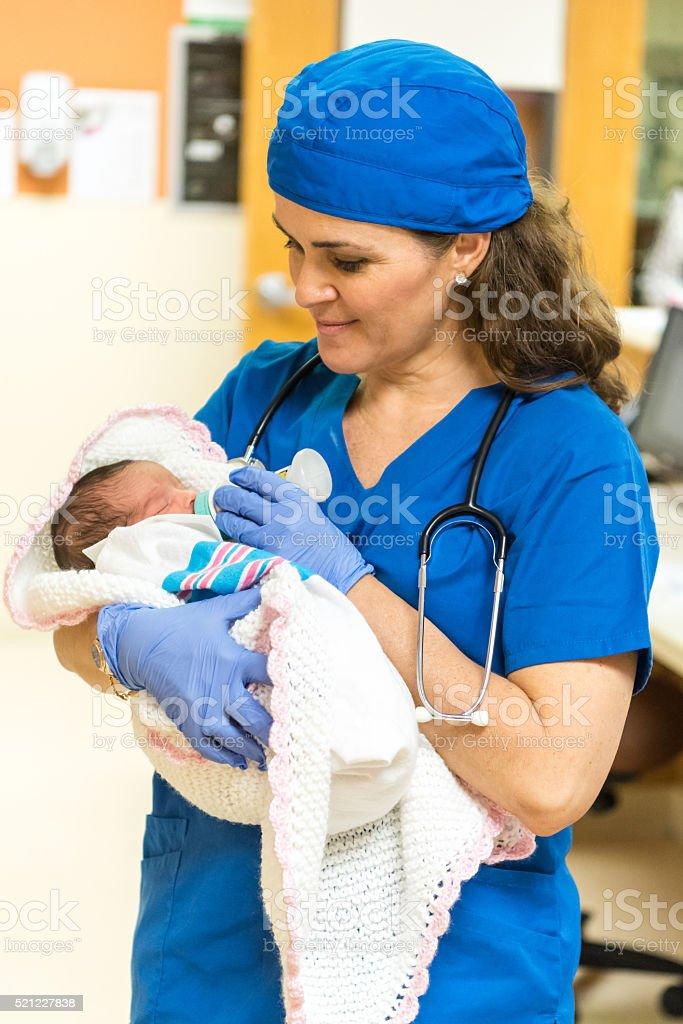 Nurse feeding a newborn stock photo