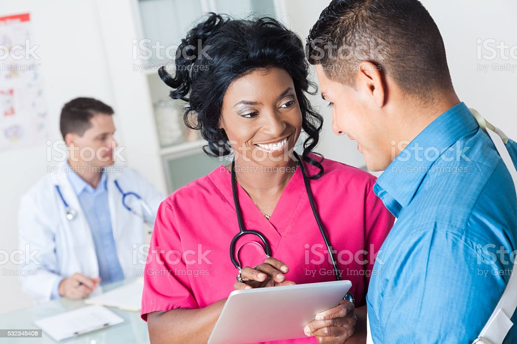 Nurse gets medical information from patient stock photo
