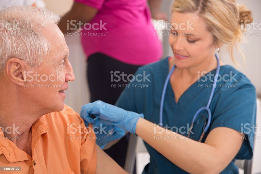 Nurse gives flu vaccine to senior adult patient at pharmacy. stock photo