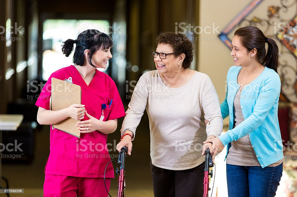 Nurse gives women tour of assisted living facility stock photo