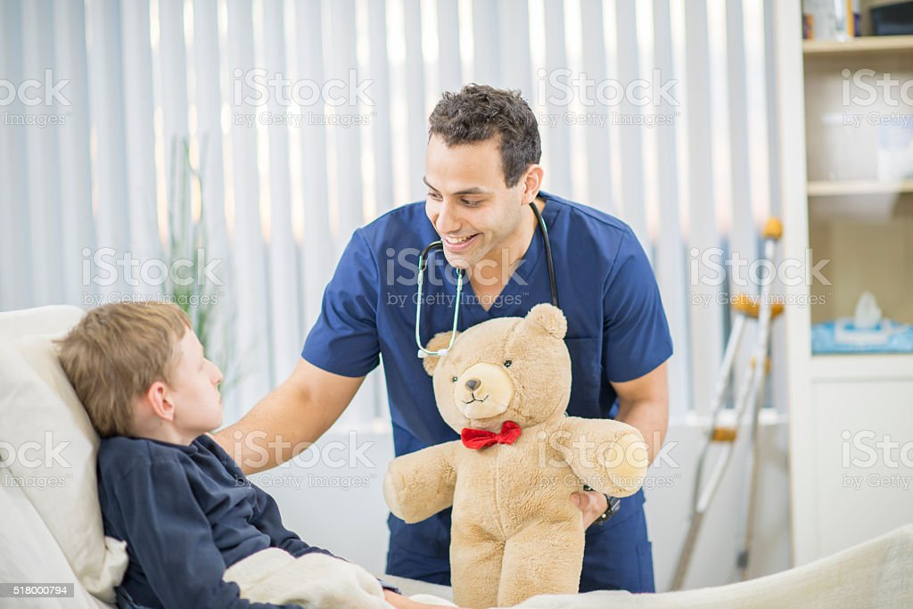Nurse Giving a Child a Gift in the Hospital stock photo