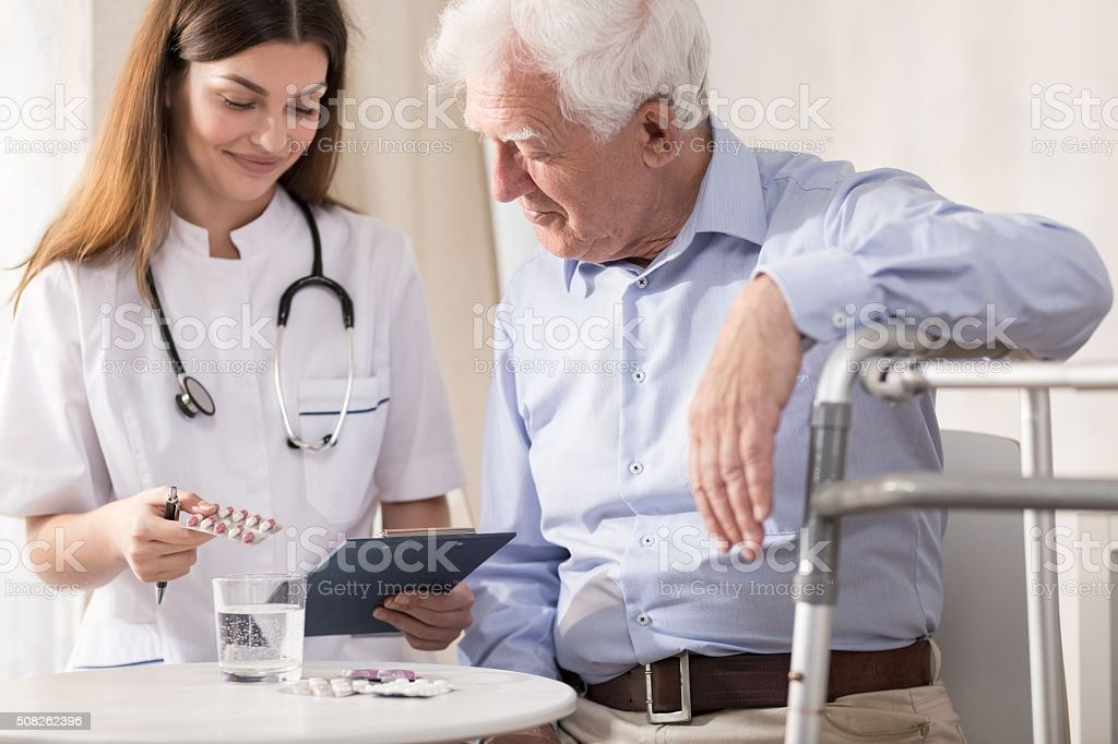 Nurse giving her patient medicines stock photo