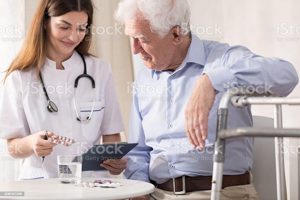 Nurse giving her patient medicines stock photo