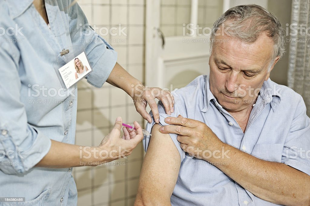 Nurse giving man vaccination royalty-free stock photo