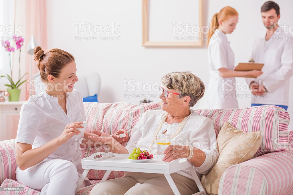 Elderly lady sitting on a couch with a tray and a young nurse giving...