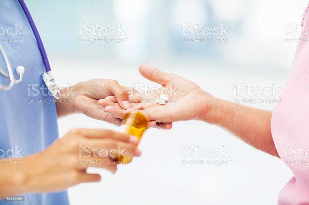 Nurse Giving Pills To Senior Patient In Nursing Home stock photo