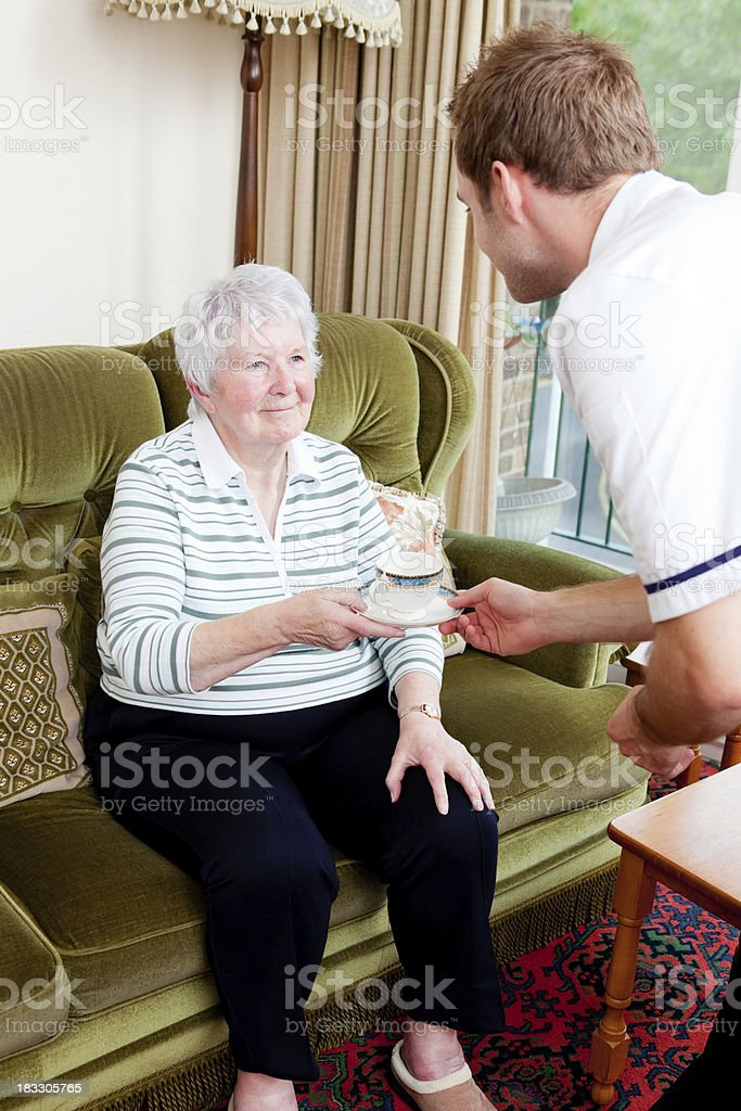 Nurse giving senior lady a drink royalty-free stock photo