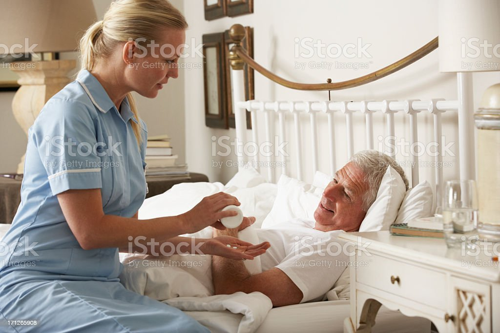 Nurse Giving Senior Male Medication In Bed stock photo