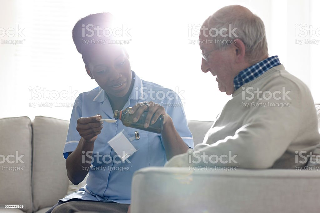 Nurse giving syrup to unwell elderly patient stock photo