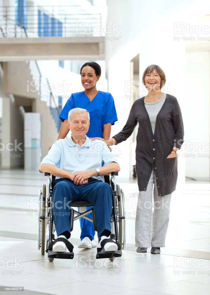Nurse helping a patient in wheelchair and his wife stock photo