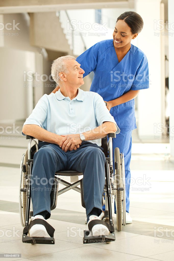 Nurse helping a patient in wheelchair stock photo