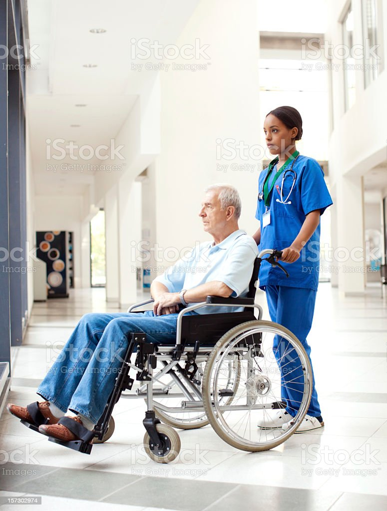 Nurse helping a patient in wheelchair royalty-free stock photo