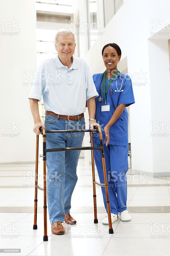 Nurse helping a patient with walker stock photo