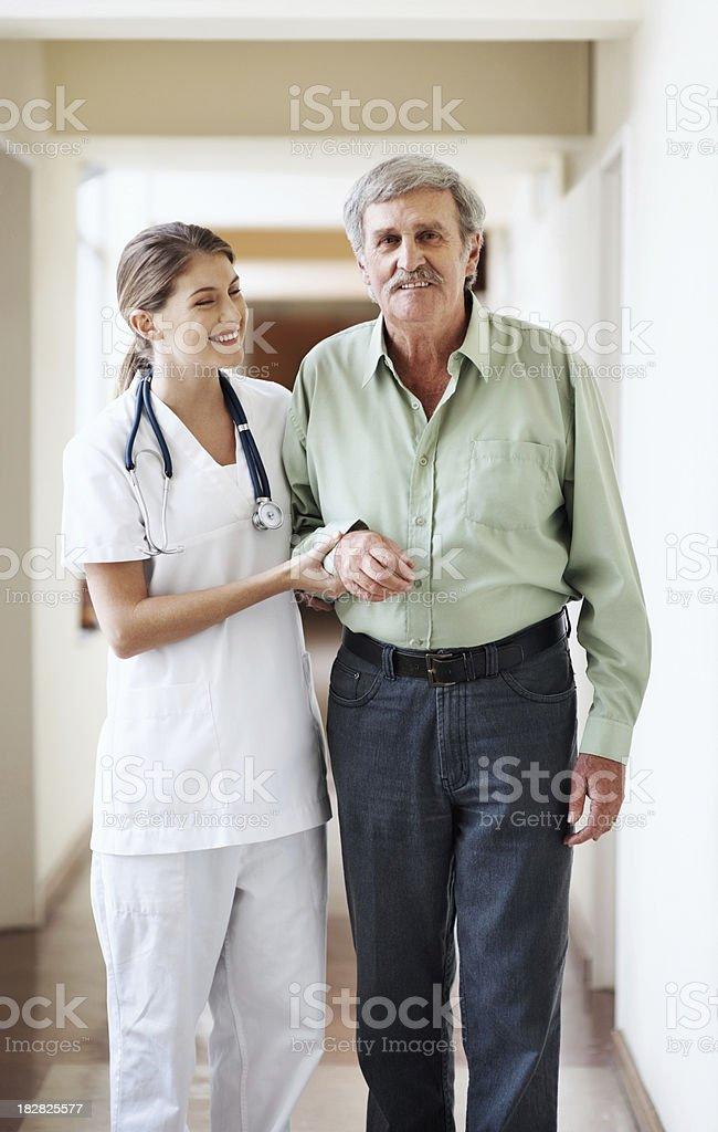 Nurse helping a senior man to walk in hospital hallway royalty-free stock photo
