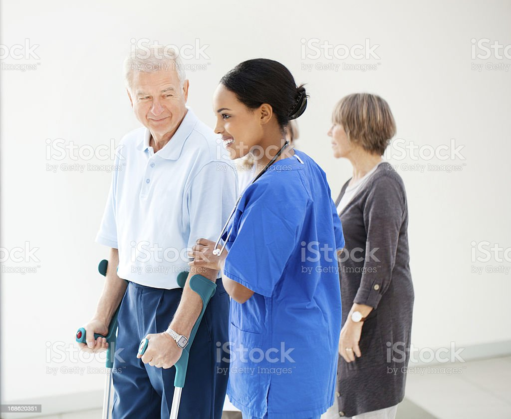 Nurse helping a senior patient in crutches stock photo