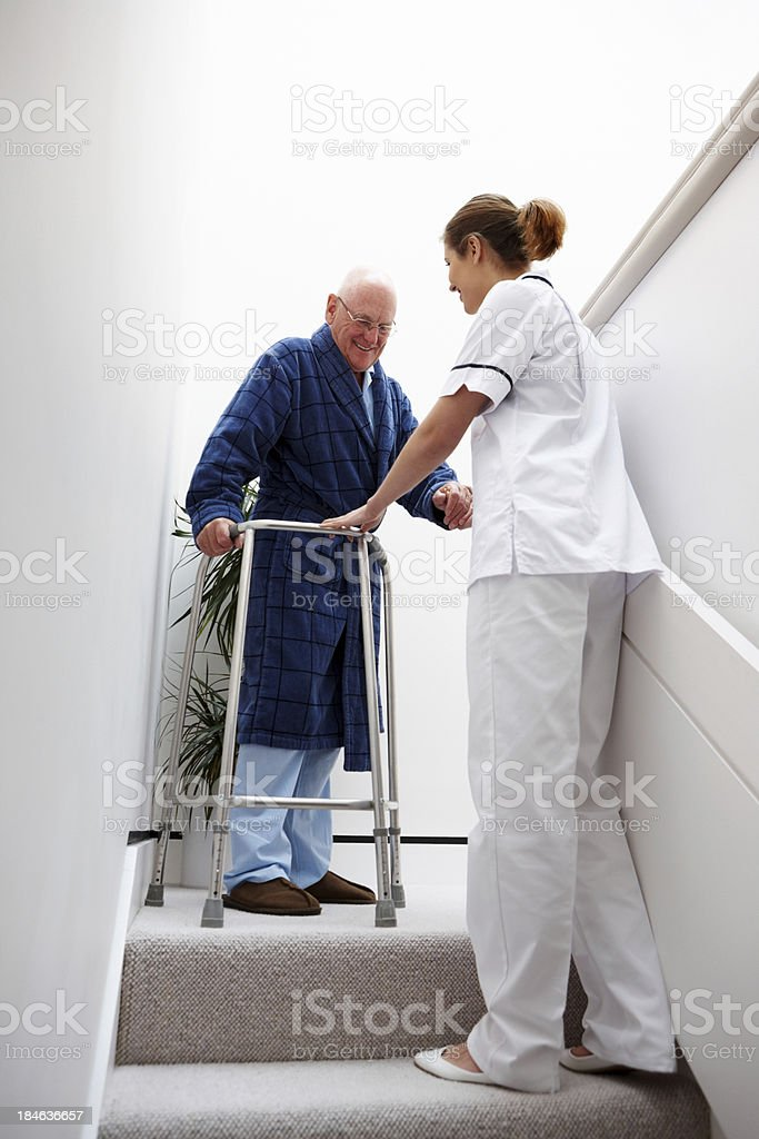 Nurse Helping an Elderly Man Down Stairs royalty-free stock photo