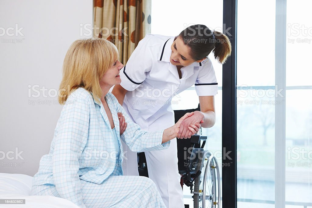 Nurse Helping an Elderly Woman Up stock photo