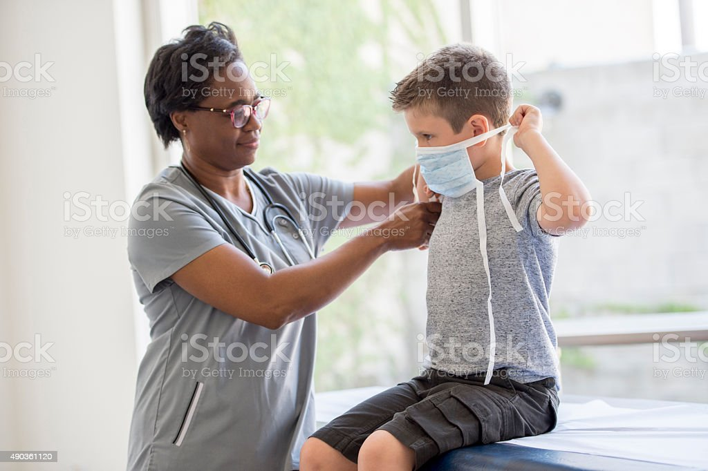 Nurse Helping Boy Put on Breathing Mask stock photo