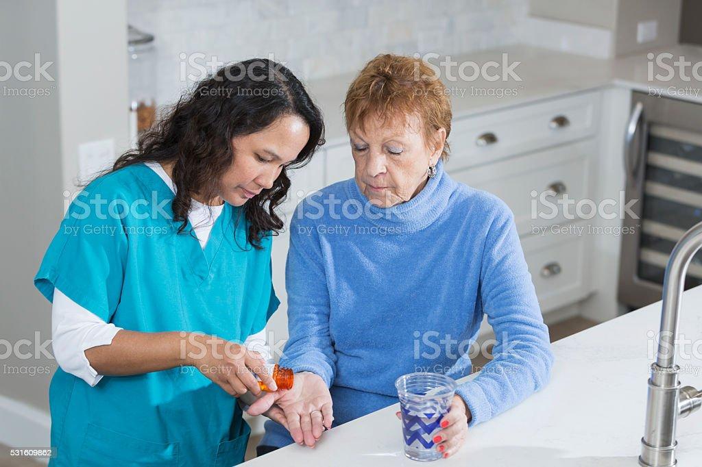 Nurse helping elderly woman take her medication stock photo